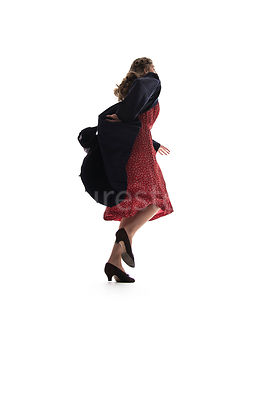 A semi-silhouette of a 1940's woman in a coat, running away – shot from low-level.