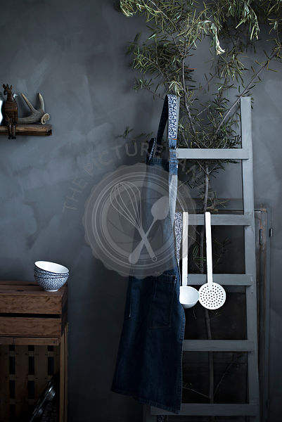 A rustic vintage kitchen with bowls, apron and utensils on a gray background