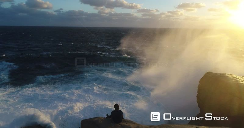 Man sitting on seaside rocks with large wave swells on the ocean Perth Australia