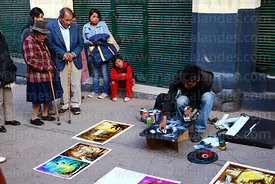 People watching spray paint artist at work in street, Cusco, Peru