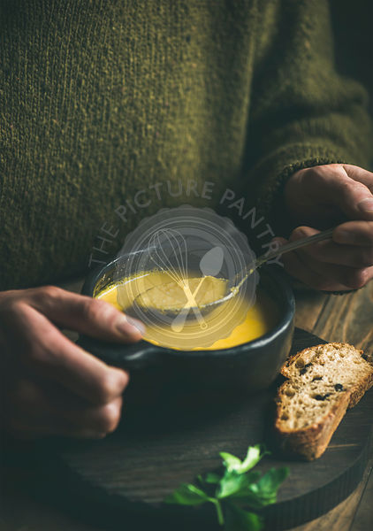 Man in winter sweater eating sweet corn soup from bowl
