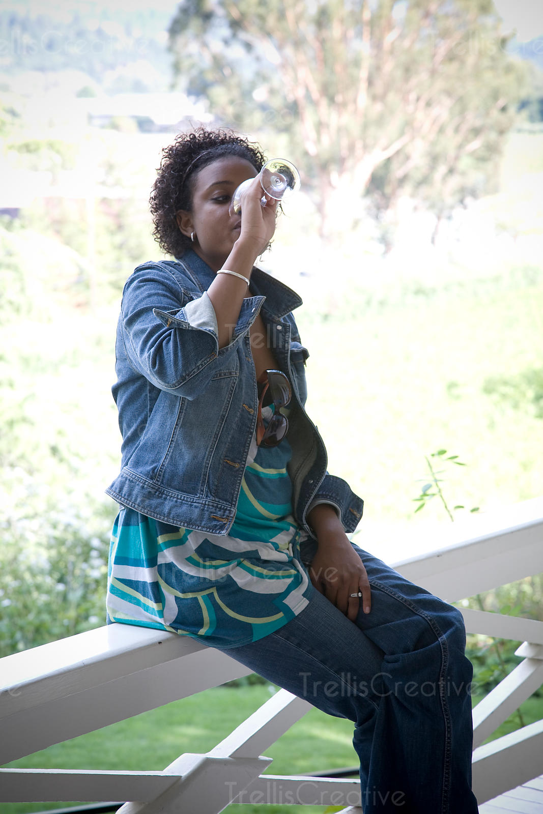 A young Black woman sips a glass of wine on a porch