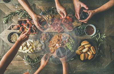 Top view of group of people having party, gathering, celebration or dinner together sitting at rustic vintage wooden table set with various wine snacks