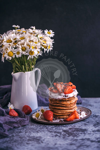 Stack of pancakes with strawberries and cream