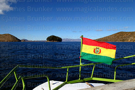 Bolivian national flag on prow of tourist boat passing Sun Island, Lake Titicaca, Bolivia