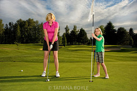 Mother and daughter on putting green; Portland, Oregon, U.S.A.