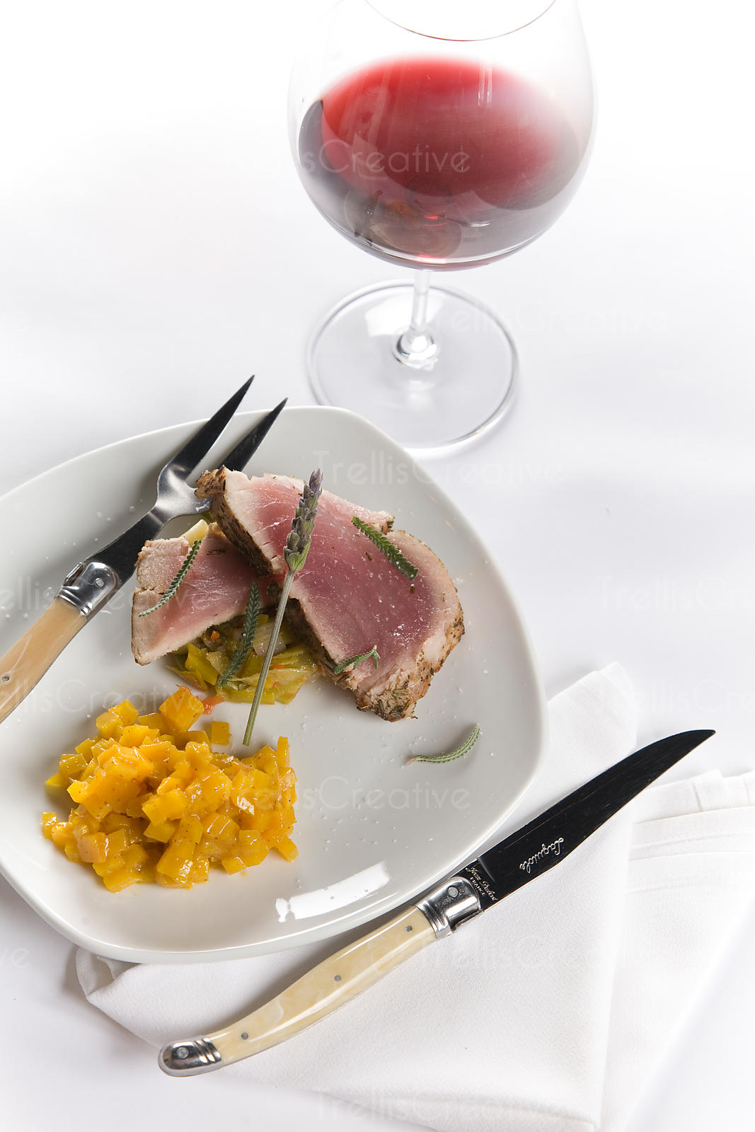Rare tuna steak served with roasted golden yellow beets and glass of red wine
