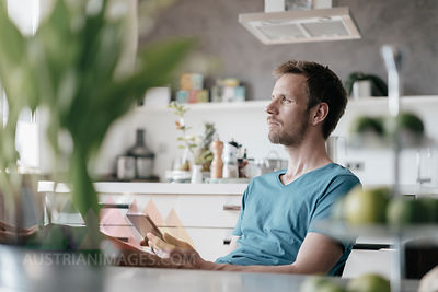 Serious man with tablet sitting in the kitchen with feet up looking at distance