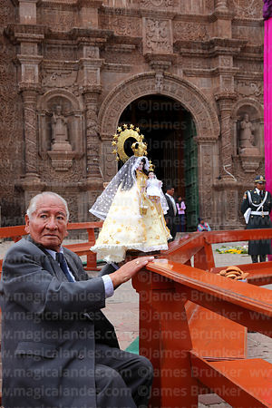 Devotee with Virgen de la Candelaria statue in special seats in front of the cathedral before central mass, Puno, Peru
