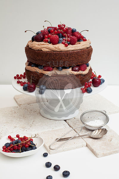 Frosted Chocolate Layer Cake decorated with fresh berries, on white cake stand
