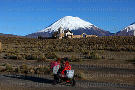 Aymara women walking along dirt track, rustic church  and Parinacota volcano behind, Lagunas, Sajama National Park, Bolivia