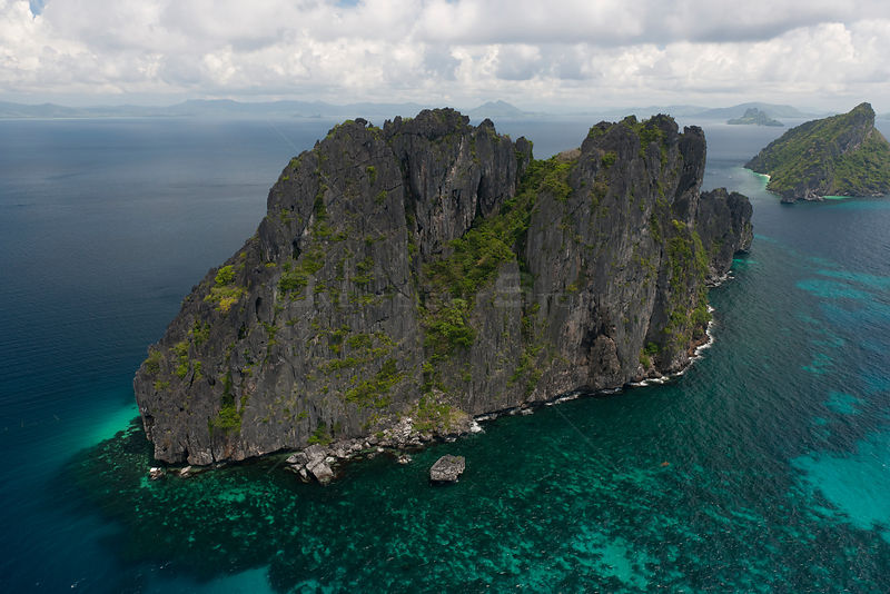Aerial view of island with steep limestone cliffs,   birds' nests amongst the caves are highly protected or guarded for their commercial value in the Chinese market, Palawan, Philippines, May 2009