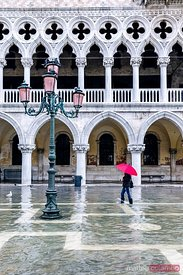 Woman with red umbrella in Venice flooded at high tide