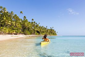 Woman on kayak near beach in a tropical island, Fiji