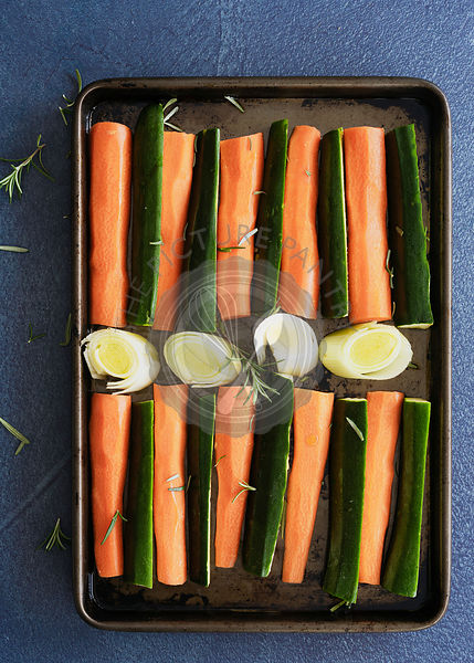 Raw carrot, zuchinni and leek on a baking tray ready for roasting.
