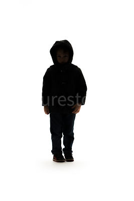 A silhouette of a boy standing in a hooded coat- shot from mid level.