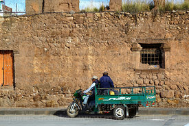 Man riding motorised freight tricycle past window of Casa de la Inquisición, Plaza de Armas, Juli, Puno Region, Peru