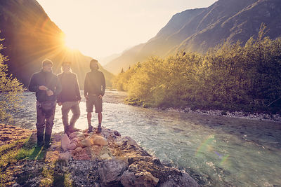 Slovenia, Bovec, three friends at Soca river at sunset
