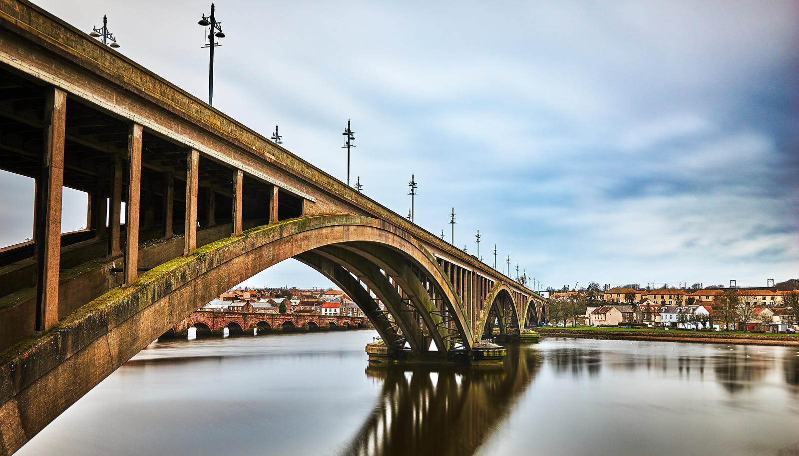 Wooden arched bridge over the river Tweed against a cloudy sky