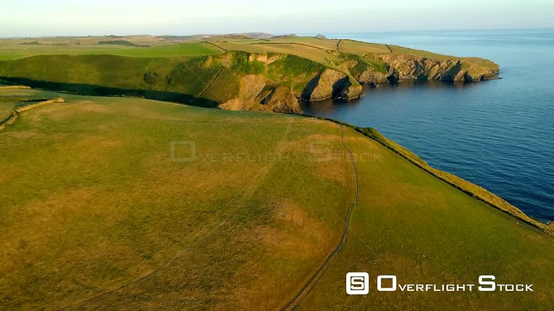 Drone camera rises over stunning headland to reveal north Cornish coast during the golden hour