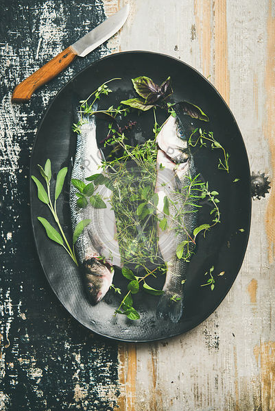 Raw uncooked sea bass fish with herbs over rustic background