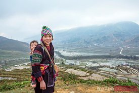 Portrait of girl of black Hmong ethnicity with her baby on the back