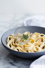 Creamy pasta in blue bowl on marble