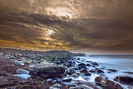 Shoreline with wet rocks and dramatic sky