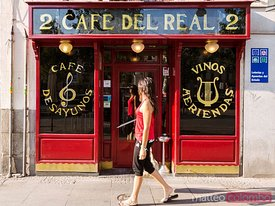 Woman walking in front of typical cafe, Madrid, Spain