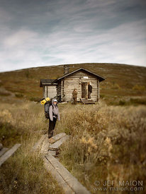 Hiker by tiny wilderness hut
