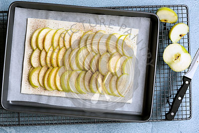 An uncooked rectangular tart with rows of apple on the pastry, a knife and cut pieces of cooking apple.