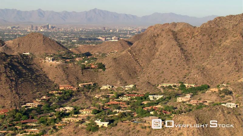 Flight over arid hills hiding pockets of residential areas to reveal Phoenix.