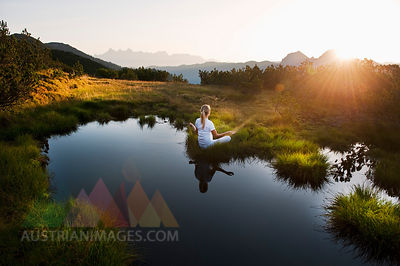 Austria, Salzburg County, Young woman sitting near mountain lake and doing meditation