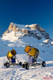 Two snow cannons on a ski slope in the alps