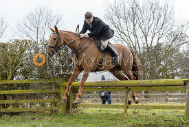 Russell Cripps jumping a hunt jump - The Cottesmore Hunt at Grange Farm