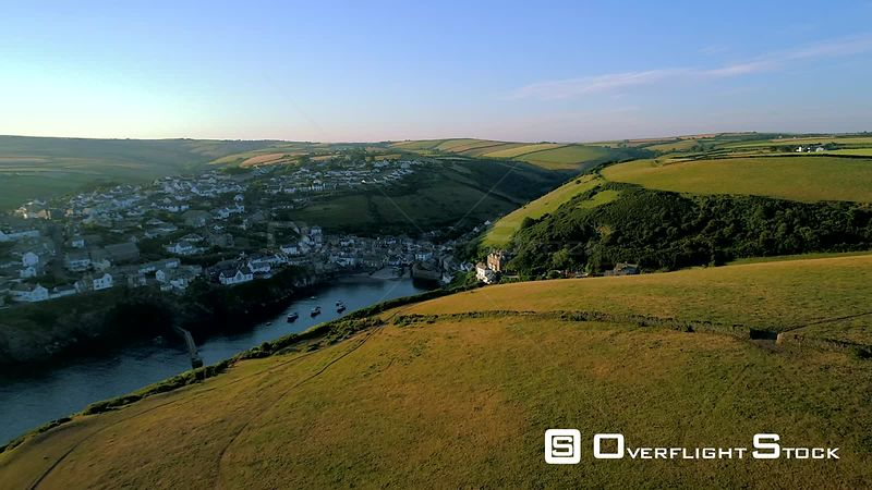 Drone flies over headland to reveal village of Port Isaac in Cornwall during the early morning light