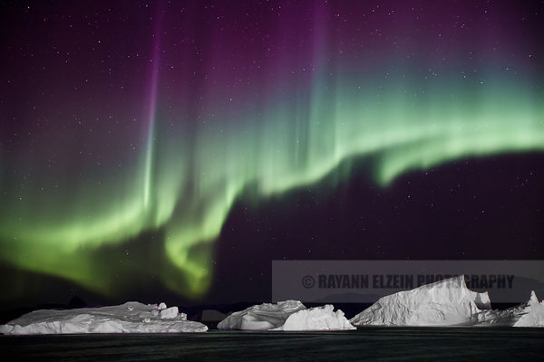 Close-up of the northern lights above icebergs in Uummannaq in Greenland