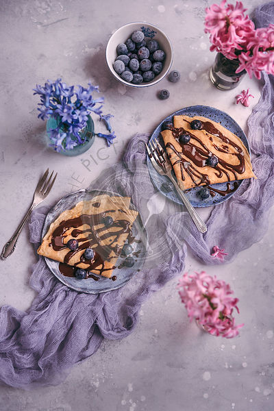 Crepes served on dessert plates drizzled with melted chocolate and topped with blueberries