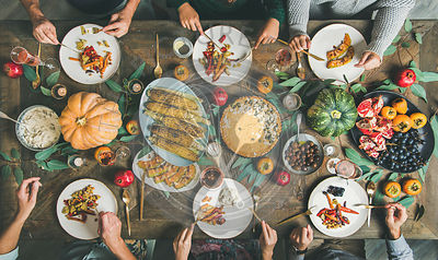 Friends eating at Thanksgiving Day table with vegetarian snacks