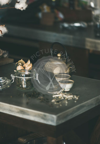 Golden iron teapot and japanese cups full of green tea
