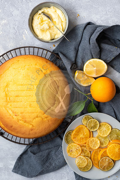 A homemade orange cake with a plate of  sliced candied citrus fruits and a bowl of butter icing.
