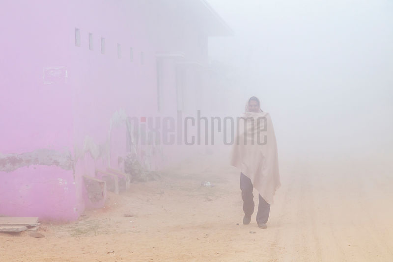 Man Walking in the Early Morning Fog