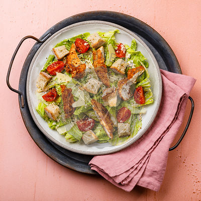 Caesar salad with Chicken breast meat on metal tray on pink background