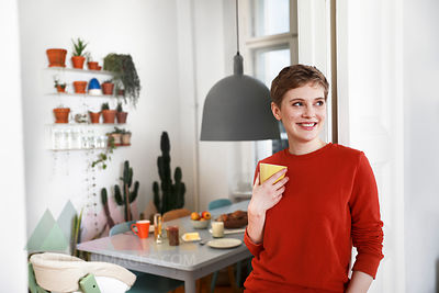 Woman standing in her comfortable home, drinking coffee