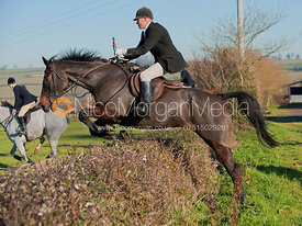 John Knowles jumps a hedge in Brooke, Rutland.