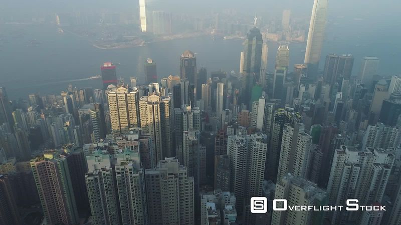 Hong Kong Skyline and Victoria Harbour. Aerial View. Drone is Flying Forward, Camera is Tilting Up. Establishing Shot.
