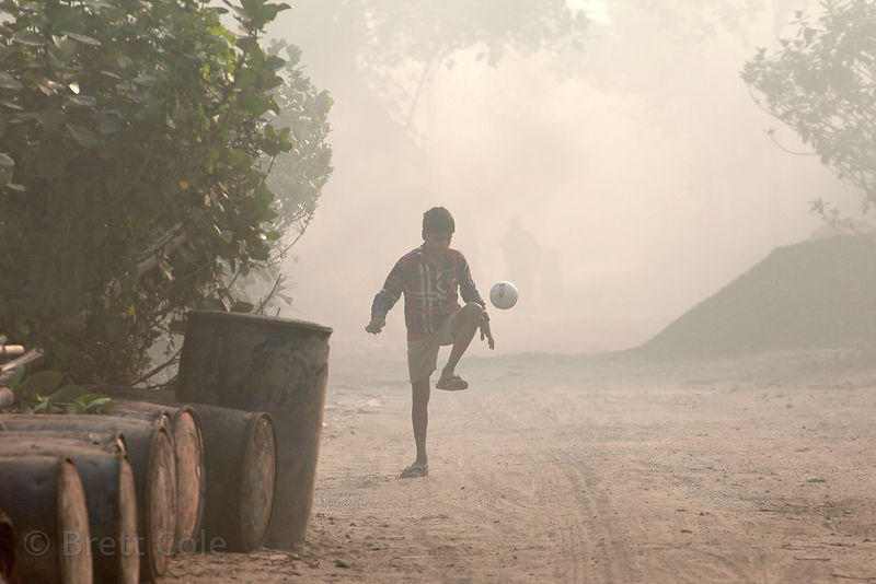 A boy dribbles a soccer ball on a dusty, polluted road in Dhapa, Kolkata, India. Dhapa is the site of Kolkata's largest landfill, and numerous recycling and incineration operations.