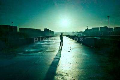 An atmospheric image of the silhouette of a mystery man, standing in an empty car park on a housing estate.