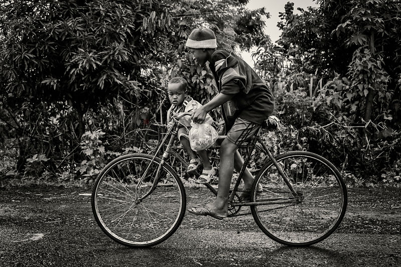 Young Boy on Bicycle with a n Infant