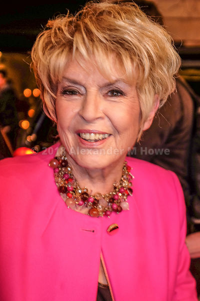 Gloria Hunniford smiling wearing  big necklace and pink jacket